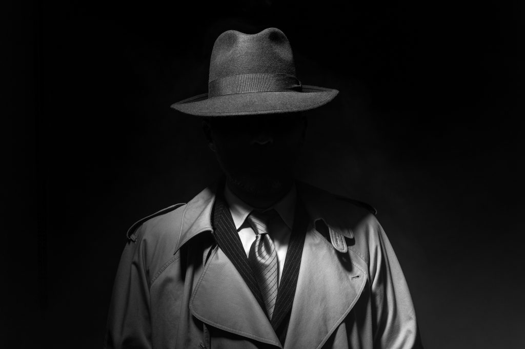 Man posing in the dark with a fedora hat and a trench coat, 1950s noir film style character, or a spy.