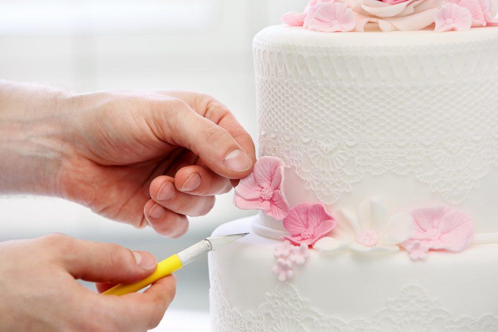 Confectioner decorates wedding cake